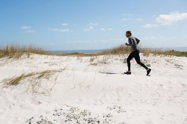 Mannelijke atleet draait op strand