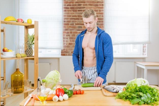 Mannelijke atleet gezonde voeding thuis in de keuken bereiden