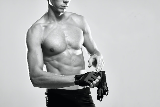 Mannelijke atleet in sporthandschoenen opgepompt perstraining fitness