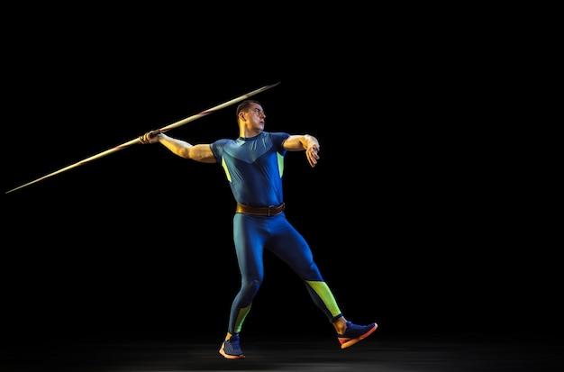 Mannelijke atleet oefenen in het gooien van speer in het donker