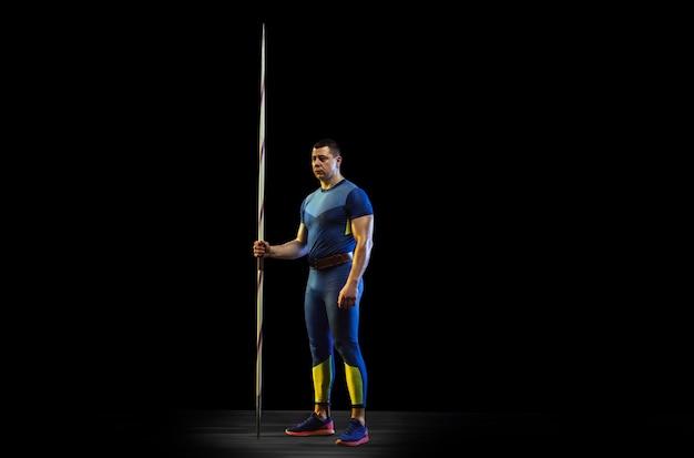 Mannelijke atleet oefenen in het gooien van speerwerpen op zwarte achtergrond in neonlicht. professionele sportman poseren zelfverzekerd. concept van een gezonde levensstijl, beweging, activiteit, competitie. copyspace.