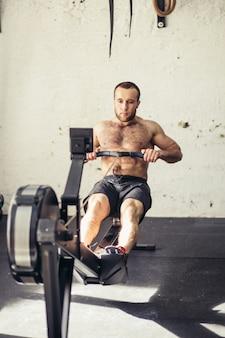 Mannelijke atleet op roeimachine op cross-concurrentie