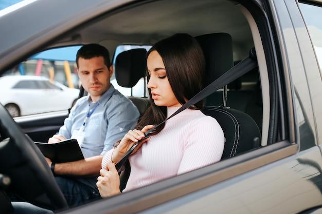 Mannelijke auto-instructeur legt examen met een jonge vrouw. de brunette houdt handen op veiligheidsgordel en sluit het. de jonge mens zit naast examenpapieren.