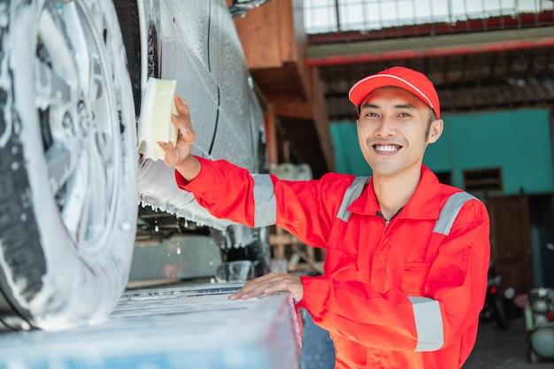 Mannelijke autoreiniger draagt een rood uniform en een lachende hoed tijdens het wassen van de onderkant van de auto in de autosalon