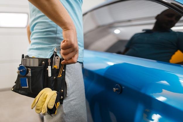 Mannelijke autowrapper met gereedschapsriem installeert beschermende vinylfolie of film op voertuigwrapping. werknemer maakt automatische detaillering. autolakbeschermingscoating, professionele afstemming
