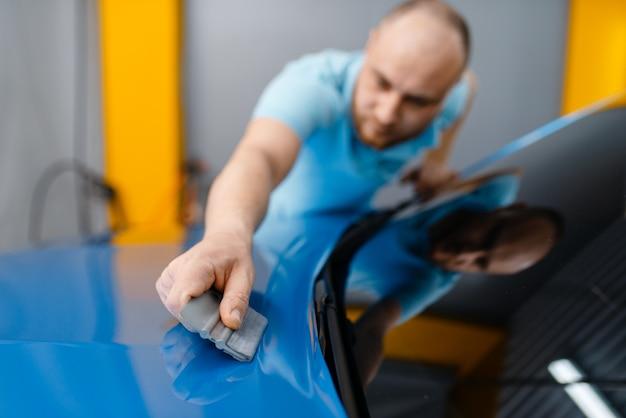 Mannelijke autowrapper met wisser installeert beschermende vinylfolie of film op de motorkap. werknemer maakt automatische detaillering. autolakbeschermingscoating, professionele afstemming