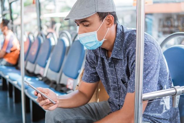 Mannelijke aziaat die mobiele telefoon gebruikt tijdens het rijden met de openbare bus of metro en gezichtsmasker draagt