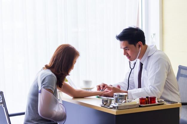 Mannelijke aziatische arts controleerde de pols van de patiënt om de afwijkingen van het hart op het bureau te controleren