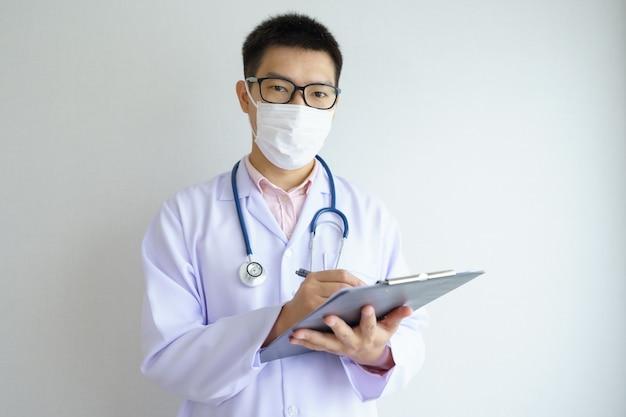 Mannelijke aziatische arts die in het kantoorziekenhuis werkt dat een gezichtsmasker draagt, beschermt covid 19-virussen.