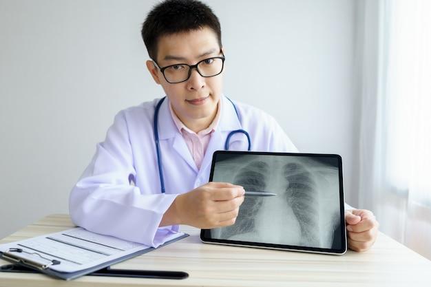 Mannelijke aziatische arts werkzaam in het kantoor ziekenhuis. x-ray bespreken met behulp van digitale tablet.