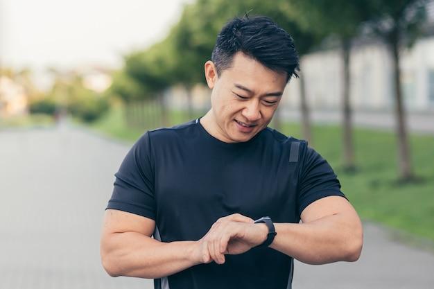 Mannelijke aziatische atleet, blij met het resultaat van de ochtendloop, rent in het park bij het stadion