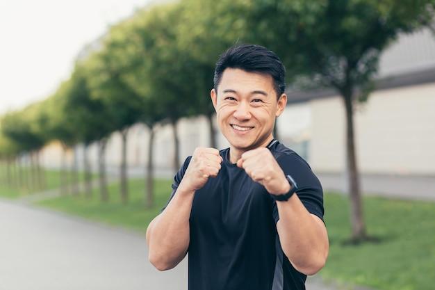 Mannelijke aziatische atleet demonstreert boksrek tijdens ochtendjoggen en fitness