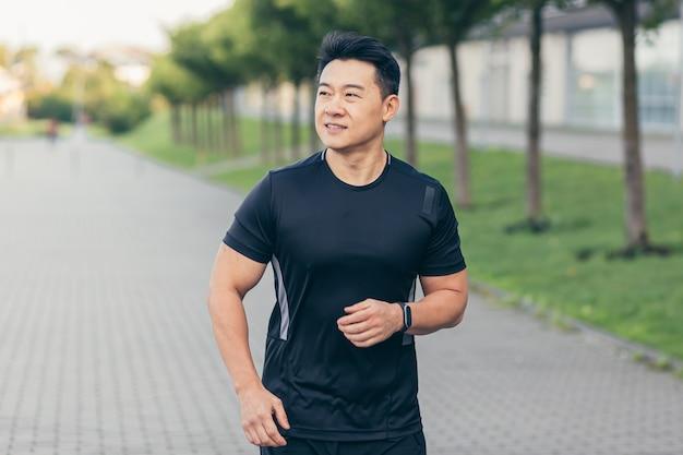 Mannelijke aziatische atleet die in het park in een rugzak rent voor het werk, die in het park bij het stadion rent