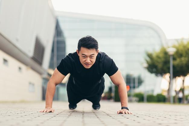 Mannelijke aziatische atleet die 's ochtends fitness doet in de buurt van het stadion duwt van de grond, verheugt zich