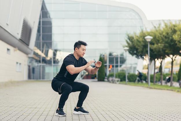 Mannelijke aziatische atleet die 's ochtends fitness doet in de buurt van het stadion