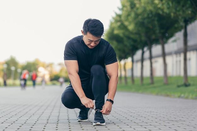 Mannelijke aziatische atleet die schoenveters aan een sneaker bindt voordat hij gaat joggen, rennend in het park bij het stadion