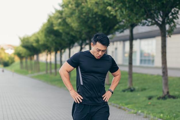 Mannelijke aziatische atleet, moe na een ochtend joggen, rent in het park bij het stadion