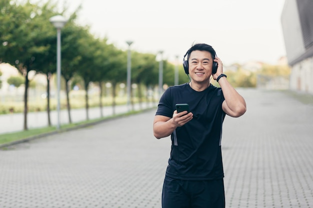 Mannelijke aziatische atleet op een ochtendrun in het park bij het stadion luistert naar muziek en podcast in grote koptelefoons gebruikt de telefoon