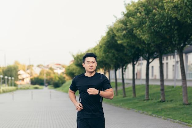 Mannelijke aziatische atleet op een ochtendrun in het park bij het stadion