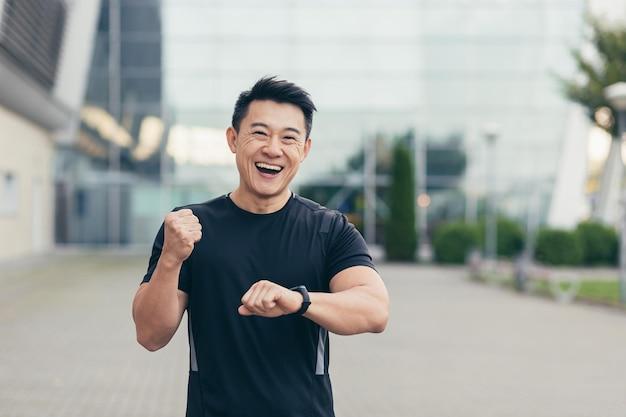 Mannelijke aziatische atleet op een ochtendrun verheugt zich over het behaalde resultaat, glimlacht