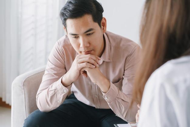 Mannelijke aziatische patiënt met het onderzoek van psycholoogvrouwen het raadplegen