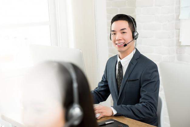 Mannelijke aziatische telemarketing klantenserviceagent die in call centre werkt