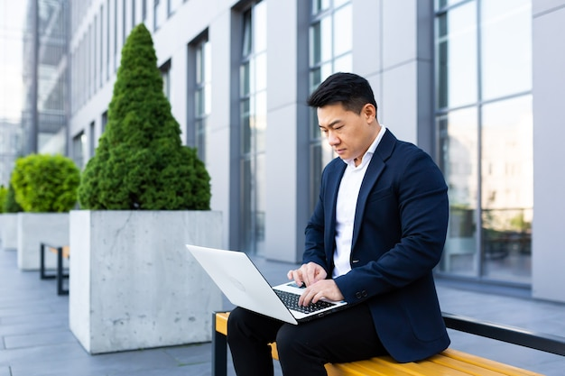 Mannelijke aziatische zakenman die aan laptop online bankieren op computer dichtbij bureaucentrum werkt