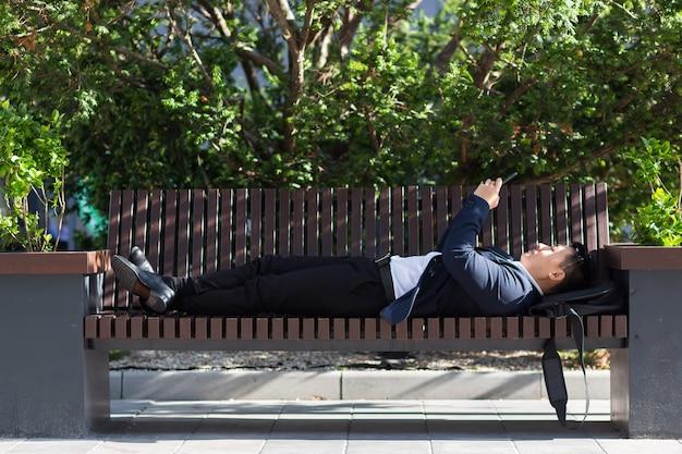 Mannelijke aziatische zakenman die op een bank ligt en rust na het werk, gebruikt een mobiele telefoon om te corresponderen en het nieuws te lezen