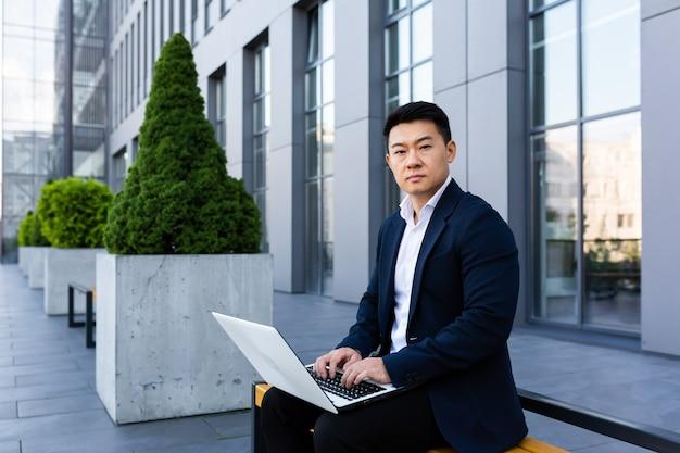 Mannelijke aziatische zakenman die op laptop online bankieren op computer in de buurt van kantoorcentrum werkt en naar camera kijkt