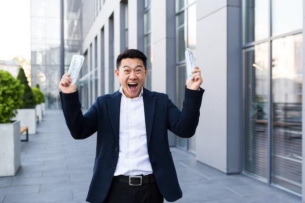 Mannelijke aziatische zakenman verheugt zich met veel contante dollars, heeft een grote overwinning en uitbetaling gekregen