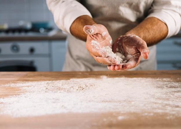 Mannelijke bakker bestrooid op houten tafel met tarwemeel