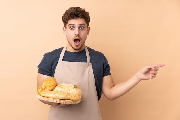 Mannelijke bakker die een lijst met verscheidene broden op beige muur houdt verrast en vinger aan de kant richt