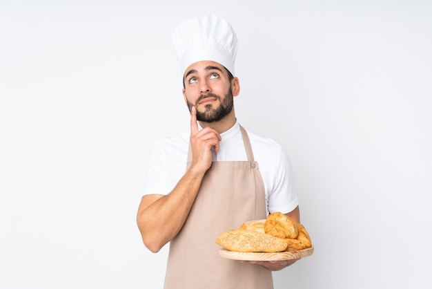 Mannelijke bakker die een tafel met verschillende soorten brood houdt die op witte muur worden geïsoleerd die een idee denken
