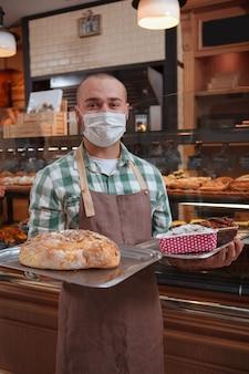 Mannelijke bakker die taarten verkoopt tijdens coronavirus-pandemie, met een medisch gezichtsmasker