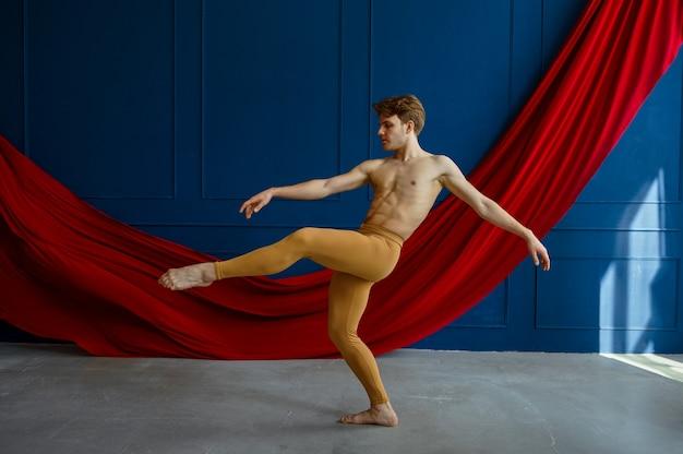 Mannelijke balletdanser, opleiding in dansles, blauwe muren en rode doek. performer met gespierd lichaam, gratie en elegantie van bewegingen