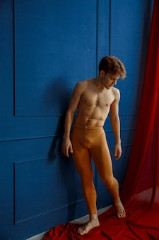 Mannelijke balletdanser poseert op blauwe muur in dansstudio, rode doek. performer met gespierd lichaam, gratie en elegantie van bewegingen