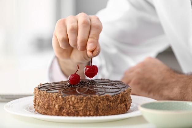 Mannelijke banketbakker die smakelijke chocoladecake in keuken verfraait