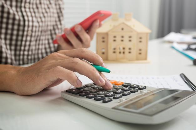 Mannelijke bankiers berekenen cijfers over belastingen op onroerend goed en onroerend goed.
