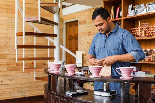 Mannelijke barista die koffie maakt met een alternatieve methode genaamd dripping.