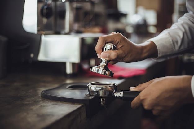 Mannelijke barista die koffie voor klant in koffiewinkel voorbereiden. cafe-eigenaar serveert een klant in de koffieshop.