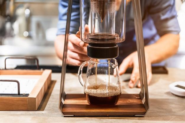 Mannelijke barista die pour-over-koffie maakt met een alternatieve methode genaamd dripping.