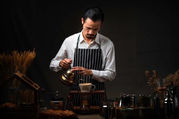 Mannelijke barista giet kokend water in het koffieglas, waardoor een kopje koffie druppelfilter wordt gemaakt