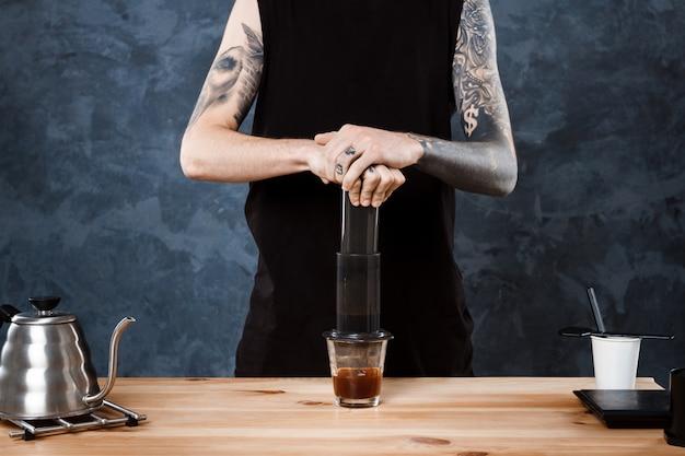 Mannelijke barista koffie brouwen. alternatieve methode aeropress.