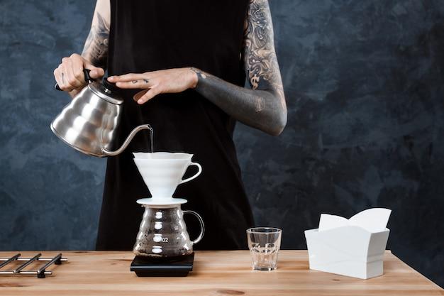 Mannelijke barista koffie brouwen. alternatieve methode overgieten.