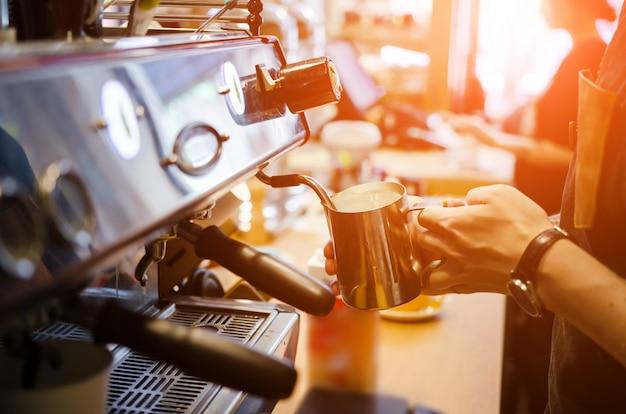 Mannelijke barista maakt koffie latte kunst in de koffie van de koffiewinkel