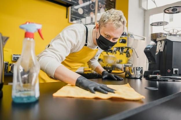 Mannelijke barista met medische masker schoonmaaktafel