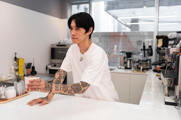Mannelijke barista met tatoeages die koffie schenkt aan de balie