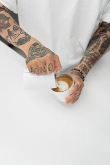 Mannelijke barista met tatoeages die melk aan koffie toevoegt