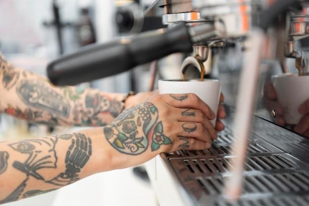 Mannelijke barista met tatoeages met behulp van de koffiemachine in de coffeeshop