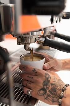 Mannelijke barista met tatoeages op het werk bij het koffiezetapparaat